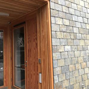 Entré på flerfamiljshus, fasad med skiffer och trä