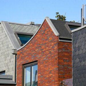 Kombination av fasadmaterial. Grå o svart rundklippt takskifferfasad möter varmröd tegelfasad.