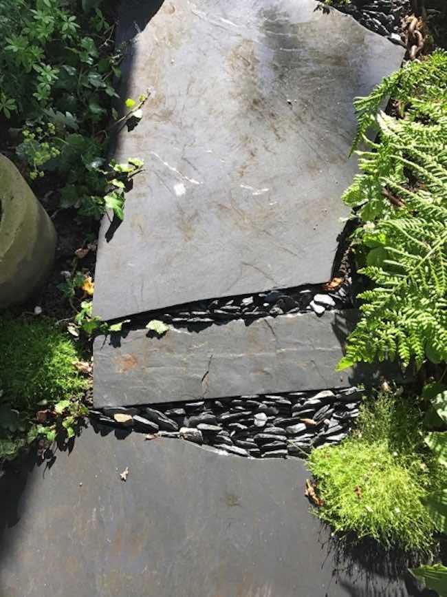 Oregelbunden svart markskiffer som trädgårdsgång